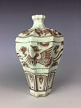 Chinese under glaze red porcelain ridged octagonal plum vessel with phoenix and floral motif.