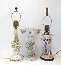 TWO FIGURAL PORCELAIN LAMPS AND CENTERPIECE, the c