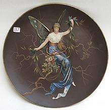 METTLACH RELIEF POTTERY PLAQUE, #1696, Woman with Butterfly Wings on Branch, full color on brown ground. Mettlach trademark underfoot, 1885-1930.  Diameter 16.5 inches.