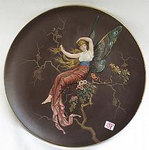 METTLACH RELIEF POTTERY PLAQUE, #1617, Woman with Butterfly Wings on Branch, full color on brown ground.  Mettlach trademark underfoot, 1885-1930.  Diameter 16.5 inches.
