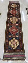 A BELOUCHI TRIBAL RUNNER, mixed hand knotted pile and flatweave techniques, five geometric medallion design, 1'11