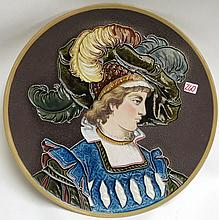 METTLACH ETCHED AND GLAZED POTTERY PLAQUE, #1411, Woman with Fancy Hat. Mettlach trademark underfoot, 1885-1930.  Diameter 16.5 inches.