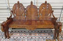CARVED MAHOGANY ELEPHANT SETTEE, India, having a triple chair back and carved elephant arms.  Dimensions:  38.25