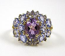 TANZANITE AND AMETHYST RING, 10k yellow gold with ten oval-cut tanzanite and 15 round-cut tanzanite set around an oval-cut amethyst weighing approximately 1.03 cts.  Ring size:  8-1/4.