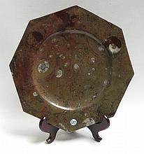 A LARGE AMMONITE FOSSIL OCTAGONAL PLATE with wood plate stand, Diameter 14 inches.