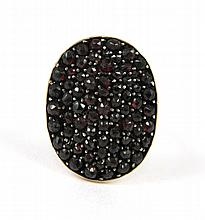 GARNET AND FOURTEEN KARAT GOLD RING, set with an oval shaped cluster of rose-cut garnets.  Ring size:  8.