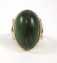 GREEN HARDSTONE AND TEN KARAT GOLD RING. The yellow gold ring features a single oval green hardstone cabochon measuring 19.6 x 12.5 x 7.0 mm deep.  Ring size:  5-1/2.