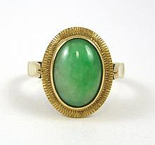 GREEN JADE AND FOURTEEN KARAT GOLD RING, set with an oval green jade cabochon measuring 10.8  x 7.75 x 2.8 mm deep. The ring is marked