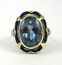 BLUE TOPAZ AND TEN KARAT GOLD RING.  The white and yellow gold ring with blue enamel forming a  frame around an oval blue topaz weighing approximately 8.56 cts.  Ring size:  7-3/4.
