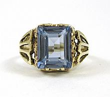 SYNTHETIC SPINEL AND TEN KARAT GOLD RING, set with a single rectangular, step-cut light blue synthetic spinel weighing approximately 3.37 cts.  Ring size:  6.