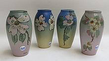 FOUR WELLER ART POTTERY VASES having matte glazed floral patterns of dogwood and wild rose, two unmarked and two with WELLER POTTERY stamp underfoot.  One signed Davis, one initialed HMC.  Heights 7 inches.