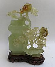 CHINESE CARVED JADE SCULPTURAL VESSEL on hardwood plinth, the serpentine jade sculpture of a covered vase beside a flowering plant, the lid and upper flower detach to reveal opening, raised on conforming carved wood plinth.  Height 9.25 inches.