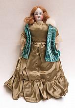 A CONTINENTAL BISQUE HEAD DOLL with blonde hair and painted features, doll has a kid leather body.  Length 15 inches.