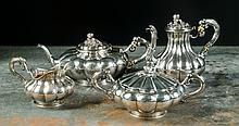 FOUR PIECE FRENCH STERLING SILVER TEA SET, late 19th/early 20th century, hallmarked French .950 Sterling, attributed to maker Paul Bouton, having melon-form body raised on ring footed bases, fruit finials, comprised of teapot, small coffee pot, cream
