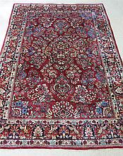 SEMI-ANTIQUE PERSIAN SAROUK CARPET, Arak region, northeastern Iran, hand knotted in a floral spray design on red ground and midnight blue border, 5'2