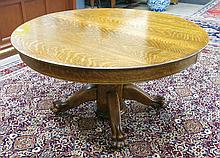 A ROUND OAK PEDESTAL DINING TABLE WITH THREE LEAVE