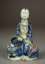 CHINESE PORCELAIN FIGURINE depicting a seated chil