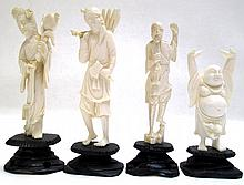 FOUR IVORY CARVED FIGURES standing on wood plinth