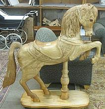 CARVED AND UNPAINTED WOOD CAROUSEL HORSE ON STAND,
