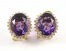 PAIR OF AMETHYST AND DIAMOND EARRINGS, each 14k  yellow gold with round-cut diamonds set around an oval-cut purple amethyst. Total estimated weight for both amethysts: 4.46 cttw.
