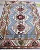 HAND KNOTTED ORIENTAL CARPET, Indo-Kazak, featuring a column of three geometric medallions on light blue ground, 5'8