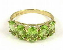 PERIDOT AND FOURTEEN KARAT GOLD RING, set with five oval-cut peridot together weighing approximately 3.76 cttw. Ring size: 9.