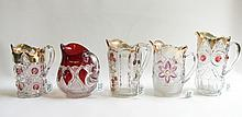 FIVE VICTORIAN GLASS PITCHERS in various patterns such as Bullseye & Fan, Flower & Cane,  a floral spray, a thumbprint and a cranberry flash teardrop. Heights from 8 to 9.5 inches.