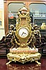 LOUIS XV STYLE FIGURE AND LYRE MANTEL CLOCK, Italian made, 20th century, the cast brass base  having a marble top and surmounted with a lyre-shaped brass mantel clock between two bronze mythological putti/goat figures.  Height - 23.75 inches.