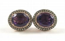 PAIR OF AMETHYST AND DIAMOND EARRINGS, each 14k rose and blackened gold with round-cut diamonds set around an oval-cut purple amethyst. Estimated weight for both amethysts: 6.80 cttw.; estimated weight for all diamonds: 0.74 cttw. Complements lots