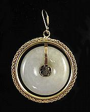 WHITE JADE AND FOURTEEN KARAT GOLD PENDANT, having a yellow gold ring around a white jade disc that centers a yellow gold Chinese character. Pendant length: 2-1/4 inches. Pendant weight: 13.5 grams.