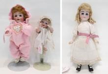 THREE BISQUE HEAD DOLLS, the first wearing pink ma