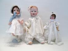 THREE BISQUE HEAD DOLLS, the brunette with the blu