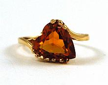 ORANGE SAPPHIRE AND TEN KARAT GOLD RING, set with