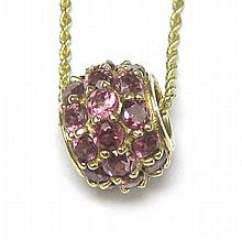 RHODOLITE GARNET AND FOURTEEN KARAT GOLD WHEEL PENDANT NECKLACE
