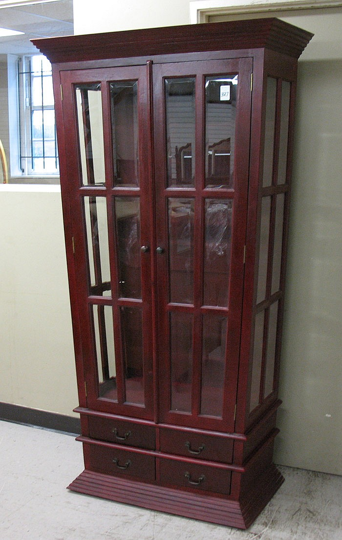 A MAHOGANY AND BEVELED GLASS DISPLAY CABINET, the