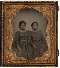 Original ambrotype photograph of two Los Angeles Latina women wearing patterned dresses, standing side-by-side, in leather case