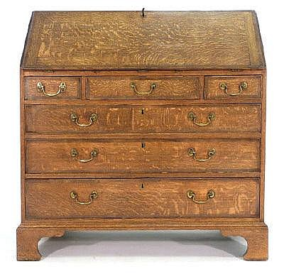 A George III oak and mahogany crossbanded bureau