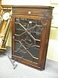 A George III mahogany hanging corner cabinet with