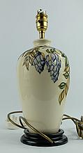 Moorcroft lampbase decorated in the Wisteria design with brass fitment on wood base, overall height 34cm