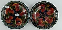 Pair Moorcroft burslem dished plates decorated in the pomegranate & berries design, diameter 22cm (small hairline crack to edge of both) (2)