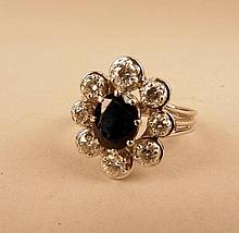 Bague en or blanc, ornée d'un saphir (sombre et un peu poli) entourée de 8 diamants taille brillant, 5,70g brut
