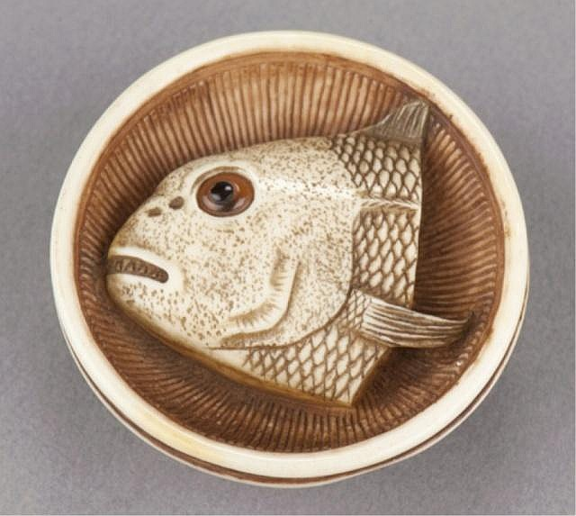 An ivory netsuke of a fish head in a bowl.