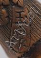 A wood netsuke of a bent over sennin.