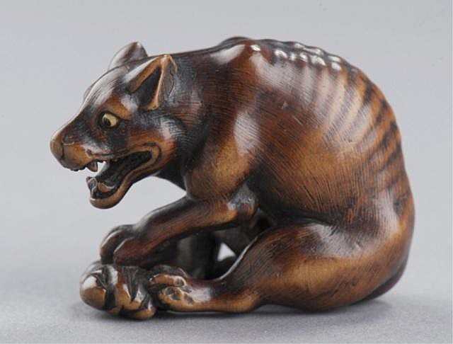 A wood netsuke of a yama-inu(wild dog).