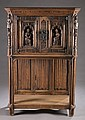 Oak Gothic revival 2 door cabinet w/ carved figs.