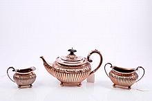 Victorian silver three piece tea set, comprising teapot of half-fluted form, with embossed scroll an