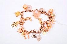 Gold charm bracelet with a collection of gold, silver and yellow metal charms