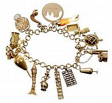 Gold charm bracelet with a collection of gold, gem set and yellow metal charms