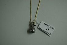 Collier articulé en or jaune, supportant en pendentif une perle grise poire (Tahiti) retenue par un motif serti de cinq diamants et trois rubis.  Hauteur: 21,8cm.  Poids brut: 9g.