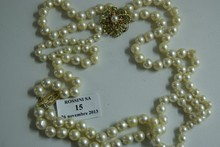 Collier triple rang de perles de culture blanches en chute, le fermoir rosace monté en or et serti de turquoises, rubis, et perle de culture centrale. Vers 1950. (défauts de surface aux perles). Longueur: environ 45cm. Diamètre des